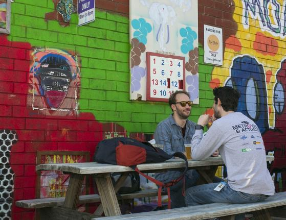 People sitting at Picnic Table Midway Mural on Graham St