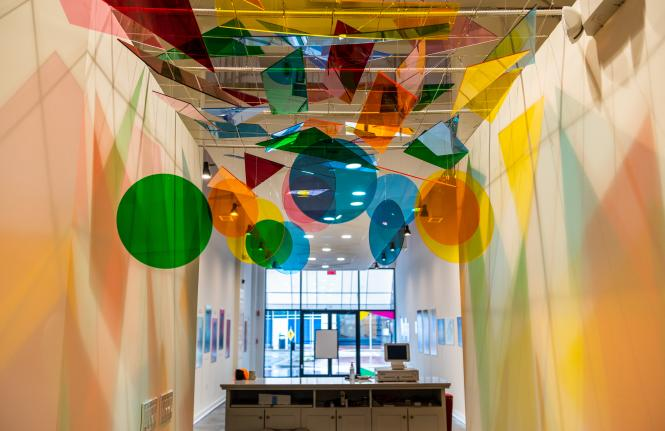 Kaleidoscope installation of multi colored plastic discs that reflect light as you walk into the space