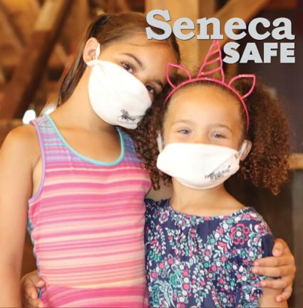 Two young girls wearing masks