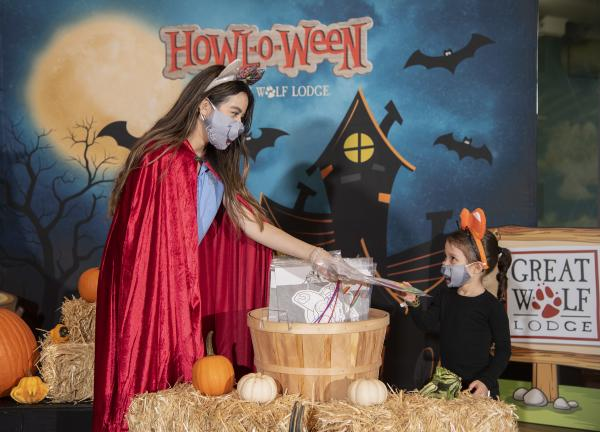 Image of one woman dressed up for Halloween, passing out a gift to a younger girl, also dressed up in a Halloween costume.