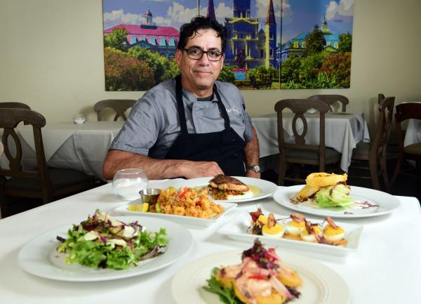 Chef Robert Vasquez, Forks & Corks, sits at a table with various dishes hehas prepared.