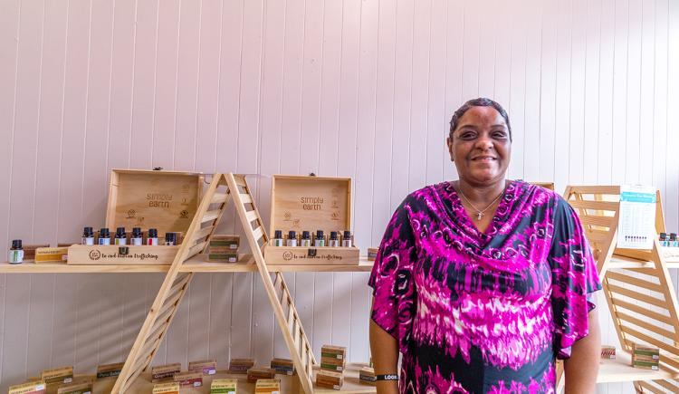 Alabaster Oils Owner Stands in Front of Product Shelves