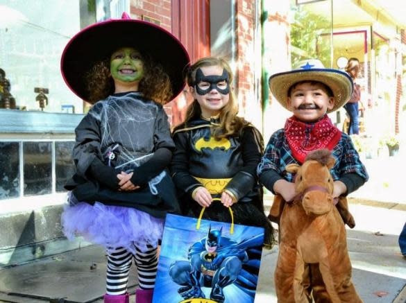 3 kids dressed in costumes at a Halloween event in Downtown Frederick