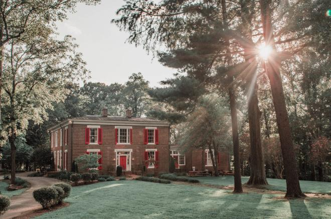Brick home with red shutters and red door sits behind a wide lawn, surrounded by pine trees as sunlight peeks through.
