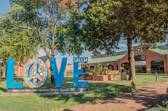 'LOVE' is spelled out in 6-ft tall blue letters. The 'O' is a peace sign filled in with colorful handprints.