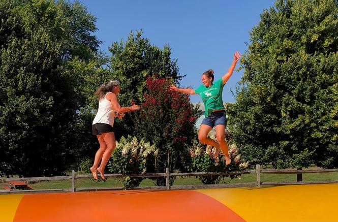 Two women jump on a jumping pillow at a Fall Festival