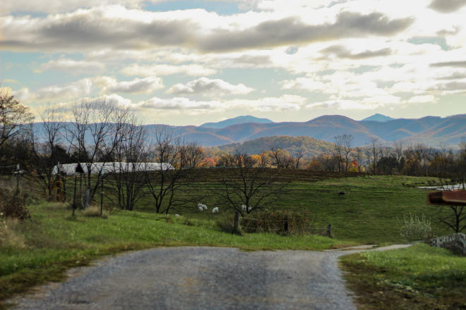 Sunlight illuminates Blue Ridge Mountains' fall color through the clouds. A gravel road and farm sits in the foreground.