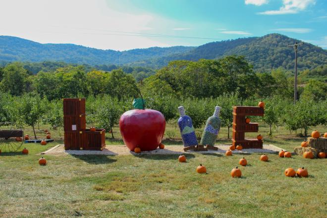 LOVEworks at Peaks of Otter Winery with Blue Ridge Mountains in the background. 'L' and 'E' are made out of produce crates, 'O' is an apple, and two wine bottle sculptures make the 'V'