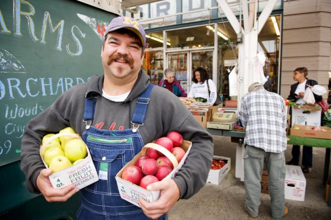 Smiling producer holding apples at Roanoke City Farmers Market