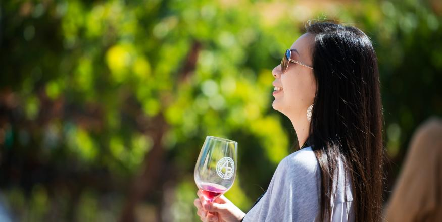 A woman with a wine glass on a SLO Cal winery tour