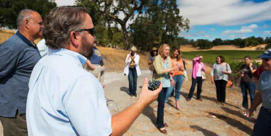 A wine tour guide presenting to a crowd at a SLO Cal winery