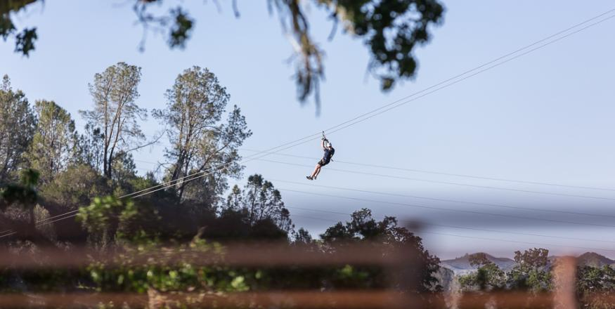 Man zip lining through the trees in San Luis Obispo