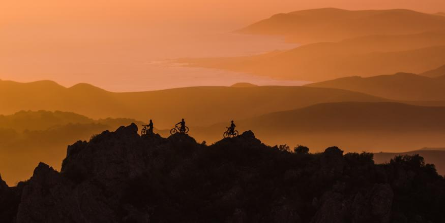 Silhouettes of mountain bikers at Cerro Alto at dusk