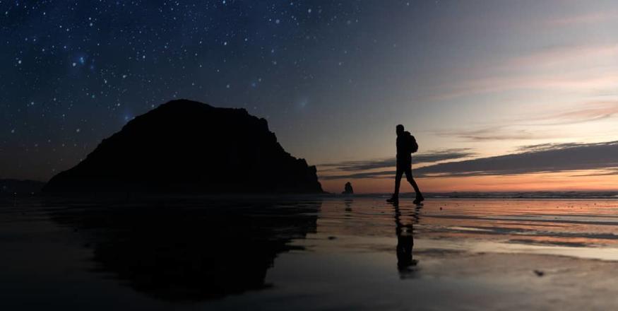 man walking beach at night