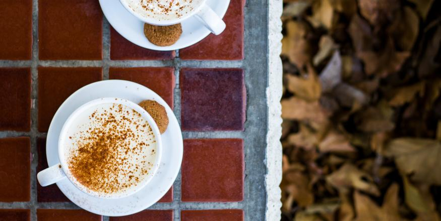 Two cups of coffee on table top with fall leaves
