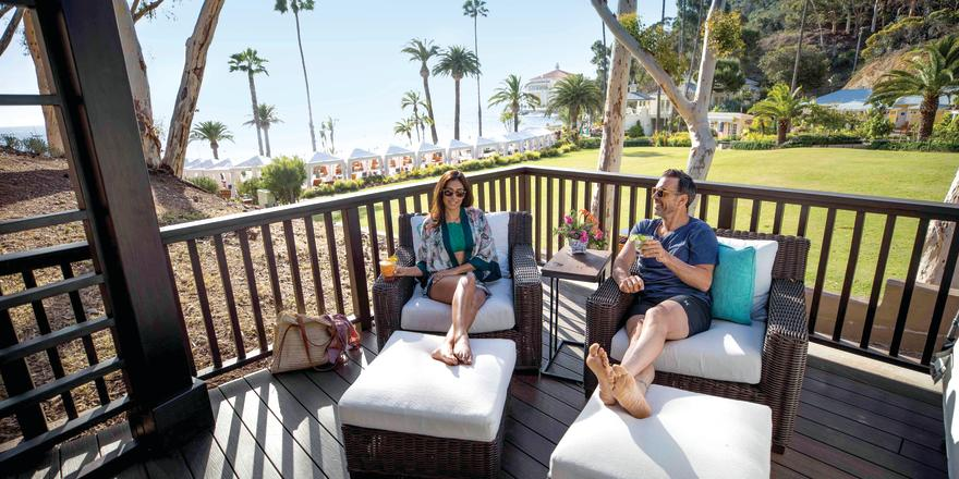 Couple relaxing on lounge chairs on a cabana at Descanso Beach Club