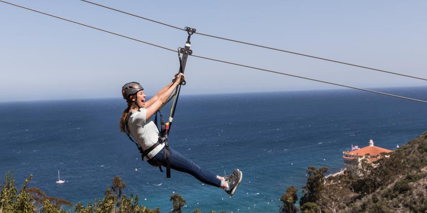 Woman on zip line tour on Catalina Island with ocean views