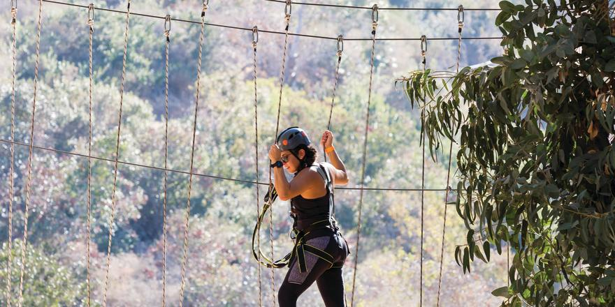 Woman crossing rope bridge on Catalina Aerial Adventure course