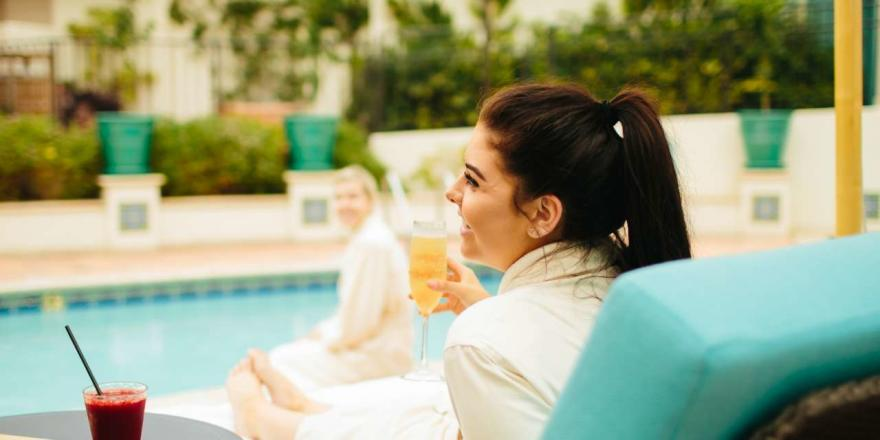 Woman relaxing on a chaise lounge with a cocktail by the pool on Catalina Island