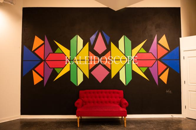 Kaleidoscope mural behind a red velvet couch