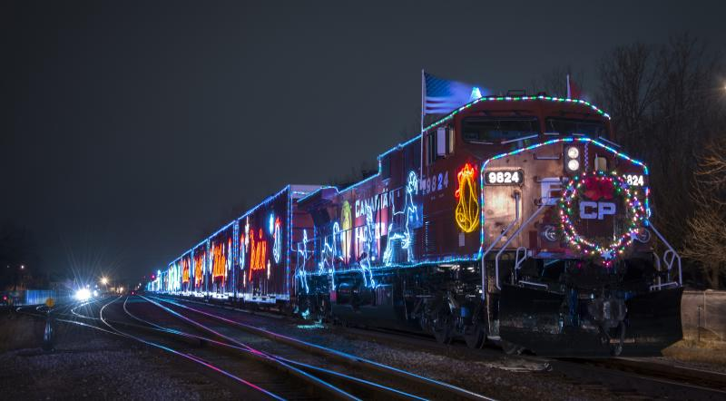 The CP Holiday Train, decorated in Christmas lights, chugs down the train tracks.
