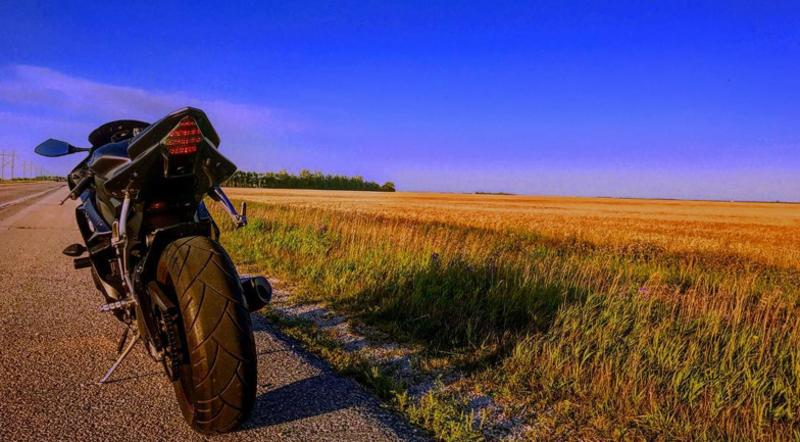Motorcycle on the side of a prairie road next to a field of wheat