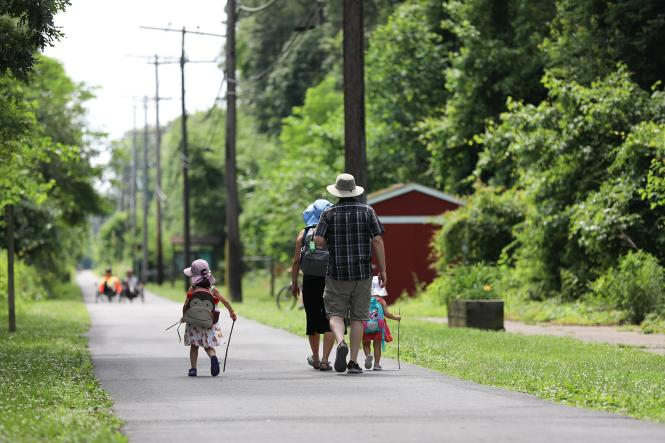 A young family walks along the B&A Trail