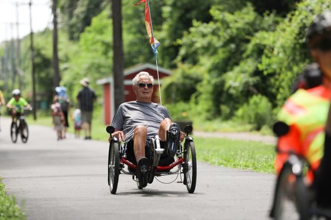 Man on a recumbent bike along the b & A Trail.