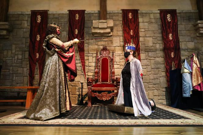 Queen Isabella knights one of her subjects.