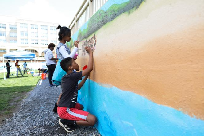 Students from the Box of Rain Program help pain the Mural of Carr's Beach at MC3