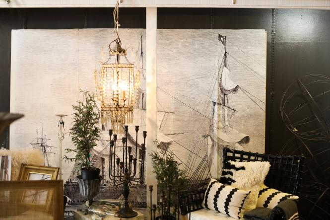 A wall mural of a tall ship, chandeliers and furniture inside Vignette.