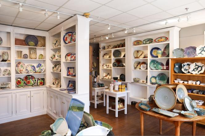 The shelves of The Annapolis Pottery are stocked with plates and pottery.