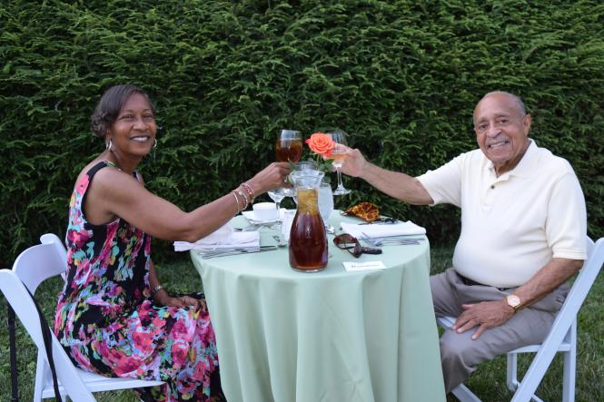 An African American couple toast to their dinner in the Paca Garden