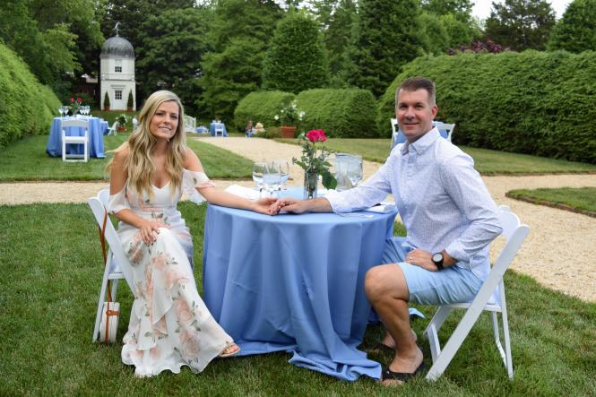 A couple holds hands at their table in Wine and Dine in the Garden