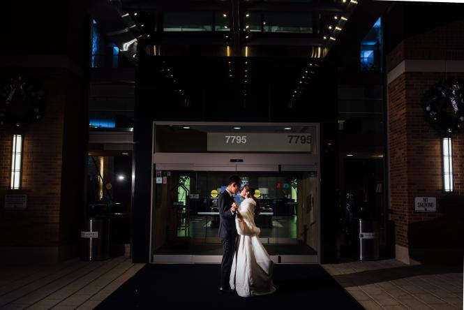 The bride and groom pose for a photo in front of the Hotel at Arundel Preserve.