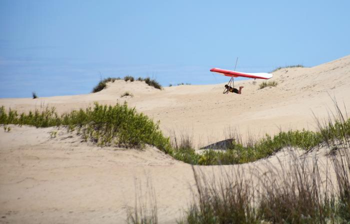 A hang glider takes flight at Jockey's Ridge State Park in the OBX