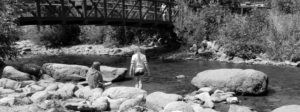 Black and white photo of kids wading in Boulder Creek