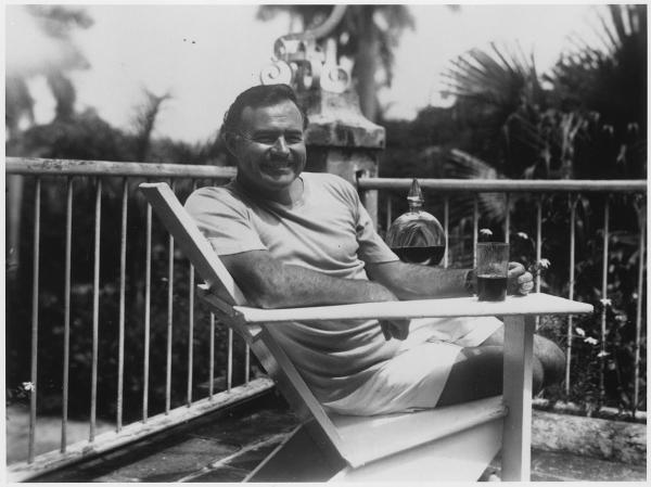 Ernest Hemingway sitting in a patio chair at his estate in Finca Vigia in Cuba
