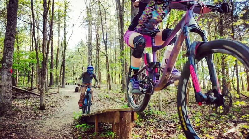 mountain bikers go over a ramp