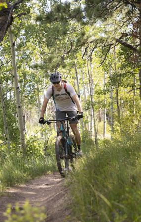 man mountain biking through the trees