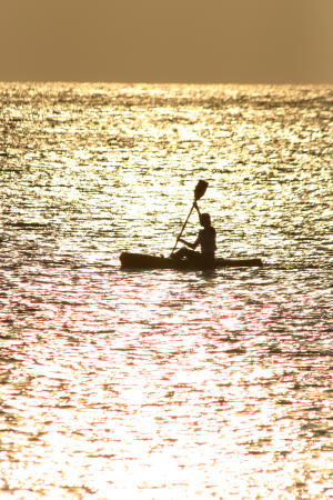 Silhouette of a single kayaker at sunset