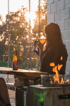 Woman enjoys the sunset while drinking a strawberry beer from Highway Manor