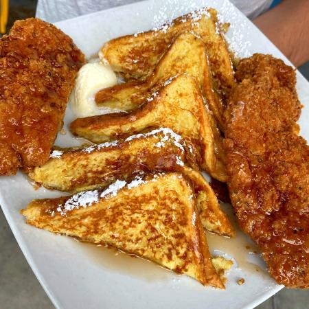 Image of five slices of french toast with two slices of fried chicken on the left and right sides. Food is topped with maple syrup, powdered sugar and butter.