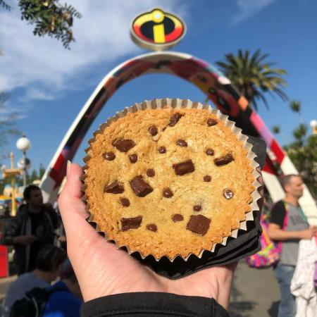 Image a cookie from Jack-Jack Cookie Num Nums being held in front of Incredicoast sign at Disney California Adventure