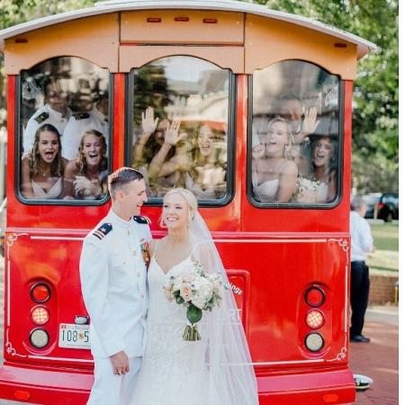 A couple poses in front of their wedding party aboard a trolley.