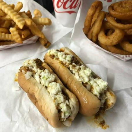 Two red hot dogs all the way laid out with fries, onion rings, and a Coke