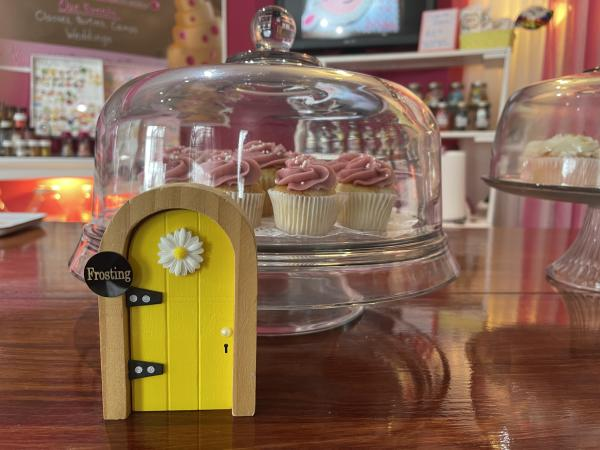 Yellow fairy door in front of cupcakes in a glass case at Our CupCakery