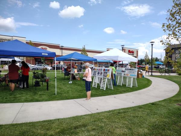 Tents set up along a curved sidewalk during the Town Green Social in Elkhart, Indiana