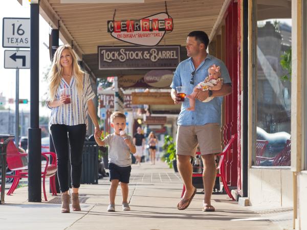 A family walks down Main Street in Fredericksburg, TX