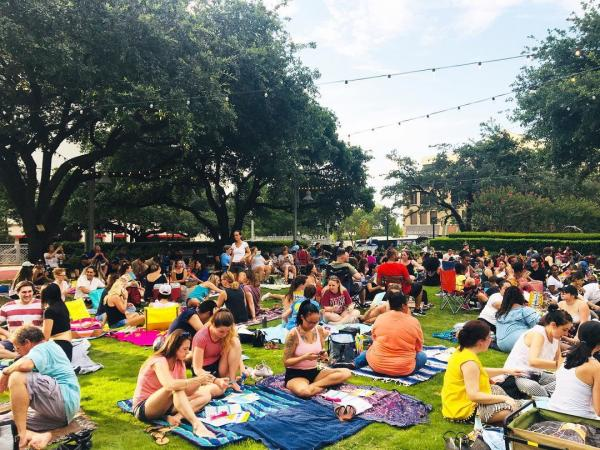Crowd Of People Sitting On Blankets At Market Square In Houston, TX